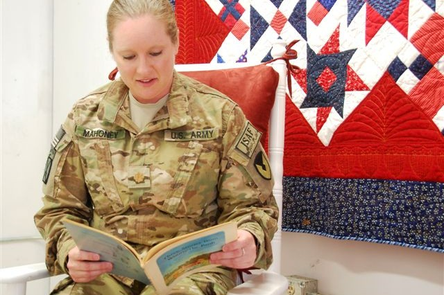 Maj. Jennifer L. Mahoney, 401st Army Field Support Brigade battle captain, looks at a vintage book available at the United Through Reading room during the grand opening July 10. The quilt was made and donated by Mahoney's mother and her quilt group, the St. Albert's Piece Makers from Sun Prairie, Minn.; and the rocking chair was donated by Patty Creque's coworkers from her home station office at Redstone Arsenal, Ala. Creque was a communications manager in the Sabre Operations Center until her recent redeployment.