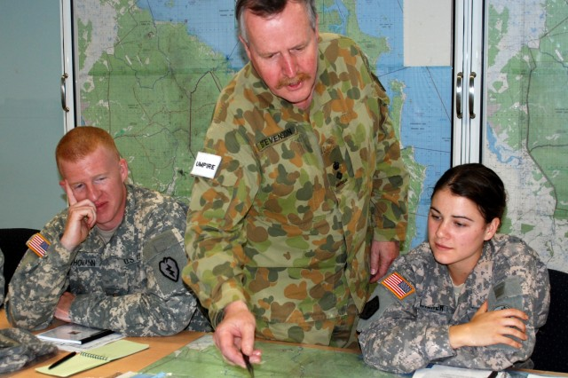 Australian Defence Force Lt. Col. Eric Stevenson, Joint and Combined Umpire liaison officer to Forces Command, (center) orients U.S. Soldiers to a local training area using a map.  Lt. Brandon Thomann, a cavalry officer assigned to the U.S. Army's 25th Infantry Division, and Capt. Kathryn Walker, an engineer assigned to U.S. Army Pacific Command, Hawaii, were taught techniques for adjudicating battlefield engagements and determine personnel and equipment casualties as umpires for Talisman Sabre on July 16, 2011.