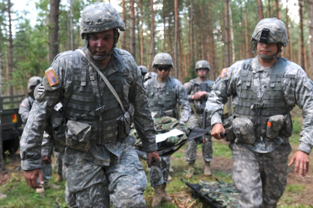 Army Sgt. Michael Tonjes, a candidate from the 8th Medical Company (Logistics), leads a litter team during a practice on Combat Testing Lane 2 of the 2011 U.S. Army Europe Expert Field Medical Badge Standardization and Testing Aug. 2, 2011 at the Grafenwoehr Training Area, Germany. (U.S. Army photo by Spc. Mary Hogle)