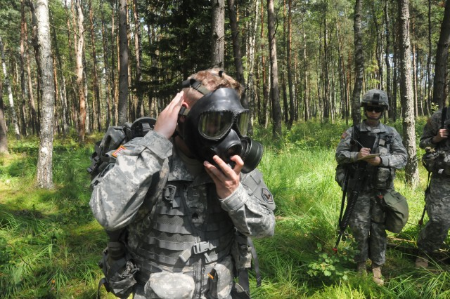 Sgt. Paul E. Zimmerman, 66th Military Intelligence Brigade and observer/controller for the 2011 U.S. Army Europe Expert Field Medical Badge Standardization and Testing, dons his chemical protective mask during an instruction period on Combat Training Lane 2, Aug. 2, 2011 at the Grafenwoehr Training Area, Germany.  Zimmerman was showing candidates Warrior Tasks that must be completed to receive a go on CTL 2, which tests candidates on their ability to perform basic Soldier skills while protecting themselves from a Chemical, Biological, Radiological or Nuclear attack. (Photo by Army Staff Sgt. Dennis Gravelle)