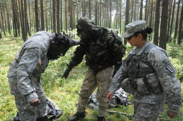 Sgt. Miriam J. Laird, 212th Combat Support Hospital, instructs candidates Sgt. Alaynna C. Davis, 212th CSH, and Spc. Christopher A. Rivner, Bravo Company, 212th CSH, at the 2011 U.S. Army Europe Expert Field Medical Badge Standardization and Testing held Aug. 1-13 at the Grafenwoehr Training Area, Germany.  Both candidates had a total of 20 minutes to decontaminate each other from a Chemical, Biological, Radiological or Nuclear Explosive attack, a main component of the EFMB Combat Testing Lane 2. (U.S. Army photo by Army Staff Sgt. Dennis Gravelle)
