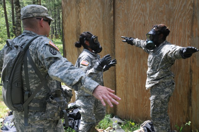 Sgt. Paul Zimmerman, 66th Military Intelligence Brigade, walks Sgt. Jazmine Velasquez and Capt. Ebony Peterman, candidates participating in the 2011 U.S. Army Europe Expert Field Medical Badge Standardization and Testing, through the correct way to remove contaminated protective gear  on Combat Testing Lane 2, Aug. 2, 2011 at the Grafenwoehr Training Area, Germany.  CTL 2 tests EFMB candidates on their ability to perform basic Soldier skills while protecting themselves from a simulated Chemical, Biological, Radiological or Nuclear attack  (U.S. Army Photo by Spc. Trisha Pinczes)