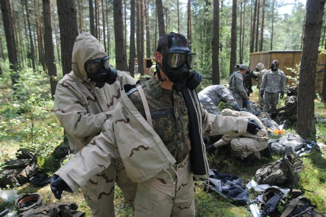 German 2nd Lt. Felix Honig, SanStff Mainz Hospital, assists German Sgt. Dustin Nicholas, 4th Company, 21st Hospital Regiment, with the removal of his chemical protective equipment during the demo phase of Combat Testing Lane 2 at the 2011 U.S. Army Europe Expert Field Medical Badge Standardization and Testing, August 2, 2011 at the Grafenwoehr Training Area, Germany.  CTL 2 tests candidates on their ability to perform basic Soldier skills while protecting themselves from a simulated Chemical, Biological, Radiological or Nuclear attack.  (U.S. Army photo by Army Staff Sgt. Thomas Wheeler)