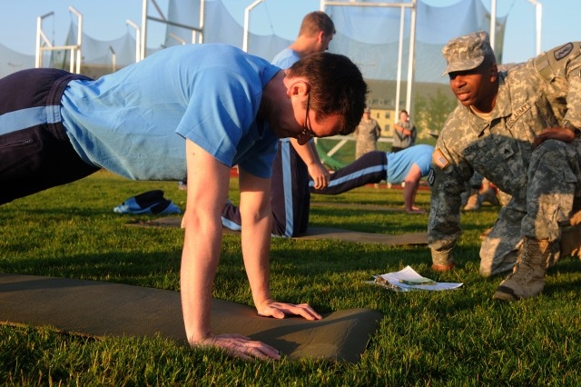German 2nd Lt. Lars Honig, a member of the Sanstff Mainz, performs a standard U.S. Army push-up during the Army Physical Fitness Test (APFT) as a pre-qualifier for the U.S. Army Europe Expert Field Medical Badge (EFMB)Standardization and Testing, July 27.  Multi-national candidates are required to meet the same standards to participate in the EFMB as U.S. Army candidates to include an APFT, qualification on an M16A2 rifle, and Basic Combat Lifesaver.  After completing these events the candidates move on to a fast-paced testing phase where they are mentally, physically and emotionally challenged. All candidates will need to successfully complete night and day land navigation, emergency medical treatment, a 12-mile foot march and other tasks to recieve the coveted Expert Field Medical Badge.(U.S. Army photo by Spc. Trisha Pinczes)