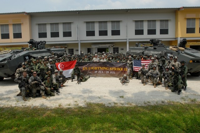 "Soldiers with the United States and Singapore armies gather for a photo, July 27, 2011, at Murai Urban Training Facility to commemorate their involvement in Exercise Lightning Strike, a bilateral combat training exercise. Throughout the exercise, Soldiers of 4th Battalion, 9th Infantry Regiment ""Manchus"" and 2nd Singapore Infantry Regiment worked together and exchanged knowledge on urban operations and weapons systems."