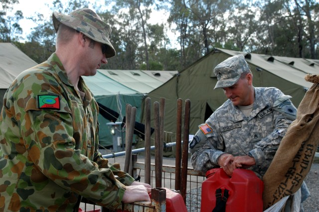 Australian Pvt. Ben Pawelski, a storeman assigned to the 9th Combat Services Support Battalion, Australian Defence Force, stationed at Warradale Barracks, Adalaide, South Australia (left) and Staff Sgt. Bryan Strother, a radio operator with the California Army National Guard's 40th Infantry Division, Sacramento (right) work together unloading fire water buckets for issue to Soldiers participating in Talisman Sabre.