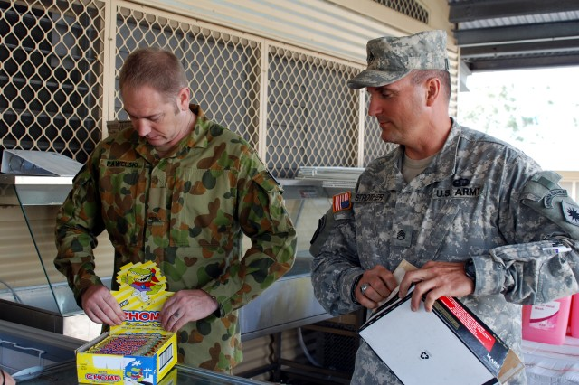 "Australian Pvt. Ben Pawelski, a storeman assigned to the 9th Combat Services Support Battalion, Australian Defence Force, stationed at Warradale Barracks, Adalaide, South Australia (left) and Staff Sgt. Bryan Strother, a radio operator with the California Army National Guard's 40th Infantry Division, Sacramento (right) work together stocking comfort items at the ""Q-store"" for military personnel participating in Talisman Sabre."