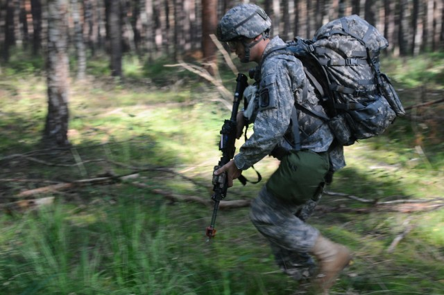 2nd Lt. Matthew Woods moves tactically through the woods during a run through of Combat Testing Lane 2 as part of the 2011 U.S. Army Europe Expert Field Medical Badge Standardization and Testing Aug. 3, 2011 at the Grafenwoehr Training Area, Germany. (U.S. Army Photo by Spc. Trisha Pinczes)