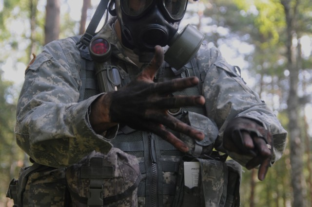 2nd Lt. Matthew Woods, a candidate in the 2011 U.S. Army Europe Expert Field Medical Badge Standardization and Testing, decontaminates his arms as part of Combat Testing Lane 2 Aug. 3, 2011 at the Grafenwoehr Training Area, Germany. (U.S. Army Photo by Spc. Trisha Pinczes)