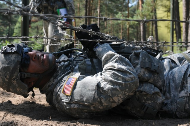 Candidate Spc. James Walters, Bavaria Dental Activity, Vilseck, Germany, crawls underneath a barbed- wire obstacle as part of Combat Testing Lane 3 for the 2011 U.S. Army Europe Expert Field Medical Badge Standardization and Testing Aug. 3, 2011 at the Grafenwoehr Training Area. (U.S. Army photo by Spc. Trisha Pinczes)