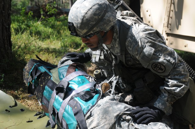 Spc. James Walters, Bavaria Dental Activity, Vilseck, Germany, a candidate in Combat Testing Lane 3 for the 2011 U.S. Army Europe Expert Field Medical Badge Standardization and Testing, transfers a casualty onto a sled for transport Aug. 3, 2011 at the Grafenwoehr Training Area, Germany. (U.S. Army photo by Spc. Trisha Pinczes)