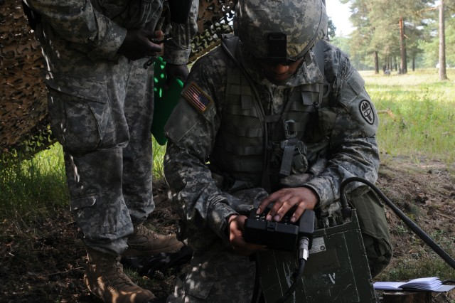 Spc. James Walters, Bavaria Dental Activity, Vilseck, Germany, a candidate for the 2011 U.S. Army Europe Expert Field Medical Badge Standardization and Testing, radios in a 9-line Medical Evacuation as Staff Sgt. Corey Hunter, an evaluator for Combat Testing Lane 3, observes Aug. 3, 2011 at the Grafenwoehr Training Area, Germany. (U.S. Army photo by Spc. Trisha Pinczes)