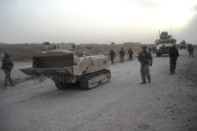 Soldiers with Alpha Company, 3rd Brigade Combat Team, 10th Mountain Division walk alongside the Doking mine clearance vehicle during a recent patrol in Zharay district, Kandahar province, Afghanistan. The Doking is a remote-controlled robotic vehicle that is used for mine clearance and route clearance, allowing operators and Soldiers to stay behind cover while the Doking is in use.