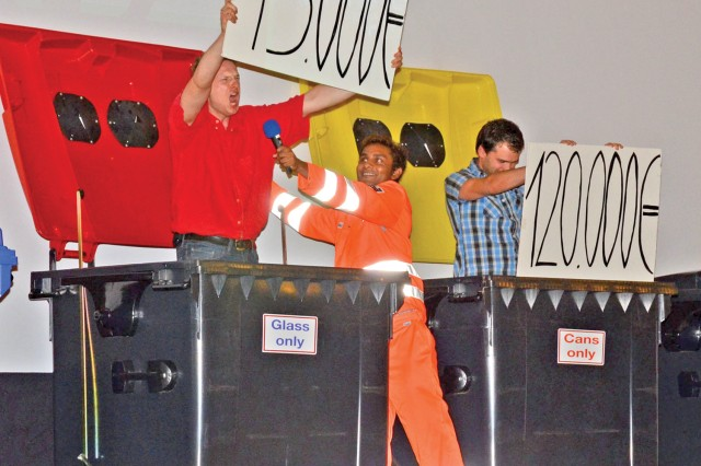 Timo Klipstein pops out of a dumpster and shouts out how much money could be saved by recycling glass as Arjun Thiru holds the dumpster lid open. At right, Ulrich Ditmar displays a sign depicting how much could be saved by recycling cans.