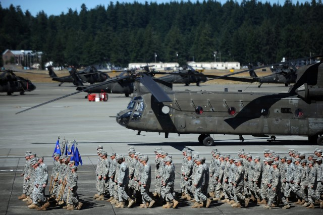 Soldiers march past a Ch-47 Chinook helicopter Aug. 1 during the 16th CAB change of command and activation ceremony at Gray Army Airfield. The aviation brigade relocated from Ft. Wainwright, Alaska to JBLM.
