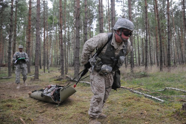 Petty Officer 3rd Class Toby League, a Navy Corpsmen from Naval Support Activity Naples, Italy and a candidate for the 2011 U.S. Army Europe Expert Field Medical Badge Standardization and Testing, pulls a casualty through the woods during part of Combat Lane 3 on Aug. 3, 2011, at the Grafenwoehr Training Area, Germany.  League is one of a handful of joint and multinational servicemembers working toward the U.S. Army medical community's most prestigious professional badge.