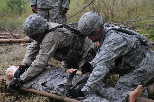 Petty Officer 3rd Class Toby League, Naval Support Activity Naples, Italy, straps a casualty onto a litter with the help of staff support as part of Combat Testing Lane 3 for the 2011 U.S. Army Europe Expert Field Medical Badge Standardization and Testing Aug. 3, 2011, at the Grafenwoehr Training Area, Germany.  League is one of a handful of joint and multinational servicemembers working toward the U.S. Army medical community's most prestigious professional badge.