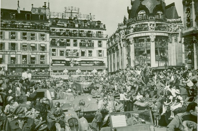 Thousands of Parisians jam the Place de L'Hotel de Ville (City Hall) in Paris, August 26, 1944, to watch the big parade for General Charles de Gualle.  Allied flags are displayed throughout the square while other civilians watch from the windows and balconies.