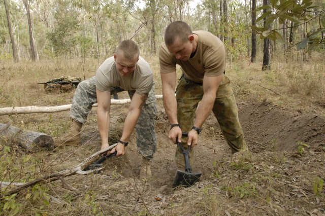 Maryland Army National Guard Sgt. Eric Ellinger and Australian Defence Force Pvt. James Adams work together to dig out a hide site during a training exercise administered by Charlie Troop, 1st Battalion, 158th Cavalry Squadron, during Exercise Talisman Sabre activities at the Shoalwater Bay Training Area, Austrailia, July 17, 2011.