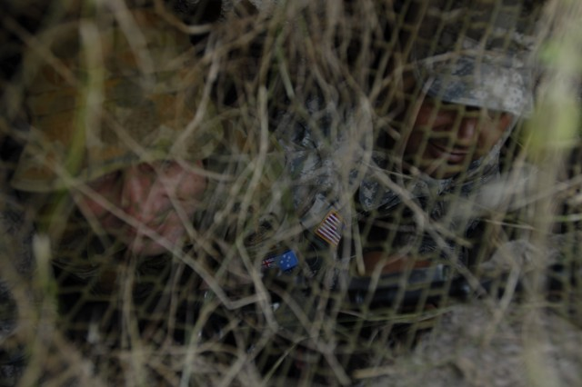 Maryland Army National Guard Staff Sgt. 1st Class Edwin Muzo and Australian Defence Force Pvt. Neal Cullinan peak out from behind the mesh net of their hide site during a training exercise administered by Charlie Troop, 1st Battalion, 158th Cavalry Squadron, during Exercise Talisman Sabre activities at the Shoalwater Bay Training Area, Australia, July 17, 2011.