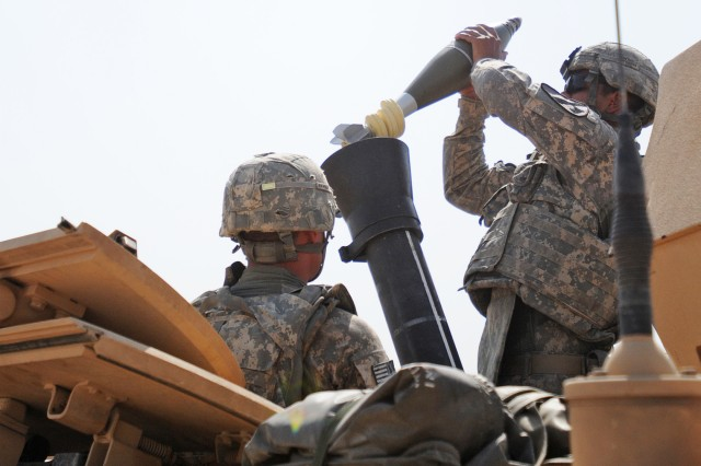CONTINGENCY OPERATING BASE WARHORSE, Iraq – Specialist Cristian Coury, right, from Marshalltown, Iowa, a mortarman with Headquarters and Headquarters Company, 1st Battalion, 8th Cavalry Regiment, 2nd Advise and Assist Brigade, 1st Cavalry Division, prepares to fire a 120mm high-explosive mortar round during a mortar operations exercise in support of Operation New Dawn at Contingency Operating Base Warhorse, Iraq, July 23, 2011.