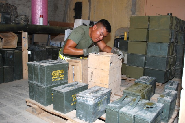 Spc. Aurelio Torres, an ammunition specialist with the 8th Ordnance Company, restores packaging for ammunition that will be re-utilized.