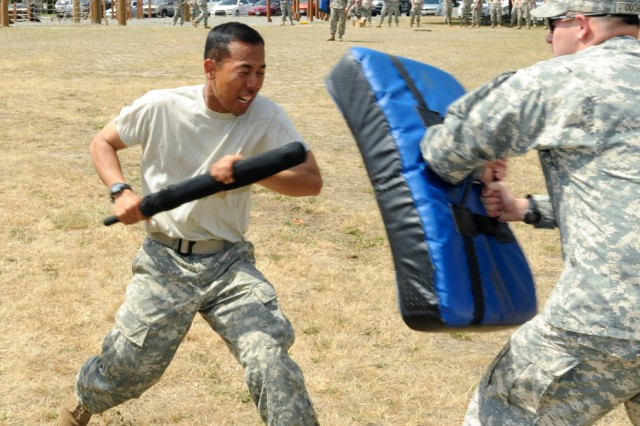 Reserve Officers' Training Corps Cadet, Okkar Pe, performs front and rear jabs with his baton during training at Joint Base Lewis-McChord, July 29. Soldiers of the 571st Military Police Company were sprayed with Oleoresin Capsicum, commonly known as Pepper Spray and then required to complete physical tasks.