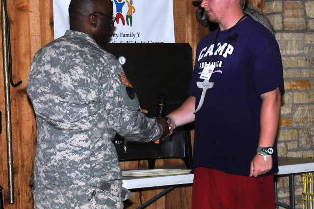 Col. Richard Dix, Army Sustainment Command chief of staff, gives a coin to a camp counselor to show appreciation during a presenation at a military children's camp in Blue Grass, Iowa, Aug. 3.  (Photo by Megan Marie McIntyre, ASC Public Affairs)