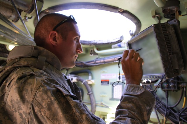 A Soldier from the 2nd Brigade Combat Team, 1st Armored Division uses the new version of the Army's friendly force tracking and messaging software, known as Force XXI Battle Command Brigade and Below, or FBCB2, Joint Capabilities Release, or JCR, inside his vehicle at the first Network Integration Exercise in June.