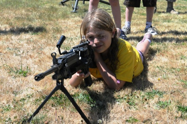 Patricia Christian, 8, learns how to get a sight picture on an M-249 squad automatic weapon. Christian was one of over 100 children of Soldiers assigned to 593rd Sustainment Brigade participating in a Kids Boot Camp, Aug. 4 at Joint Base Lewis-McChord. (U.S. Army photo by Sgt. Mark Miranda)
