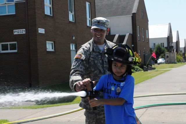 Spc. Brian Fike, a firefighter with 63rd Ordnance Battalion, teaches Juan Pablo, 9, how to use a fire hose. Pablo was one of over 100 children of Soldiers assigned to 593rd Sustainment Brigade participating in a Kids Boot Camp, Aug. 4 at Joint Base Lewis-McChord.