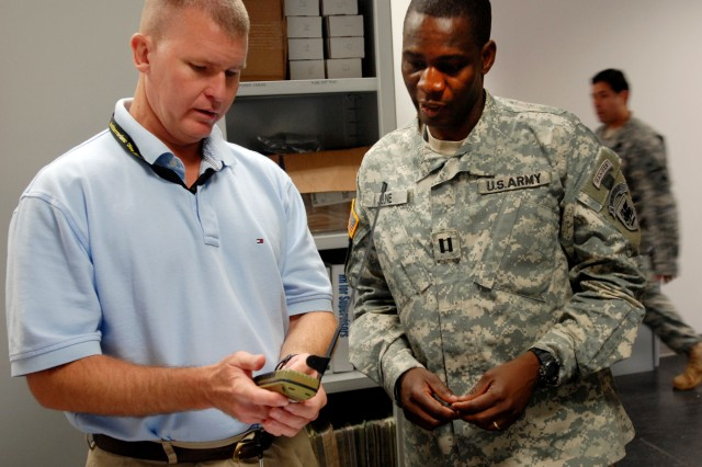John Bratcher, personnel recovery specialist (left) demonstrates a personal locator beacon for Capt. Spenger Jeune. U.S. Army Africa travelers are encouraged to visit the Personnel Recovery Directorate to take advanted of survival tools and training.