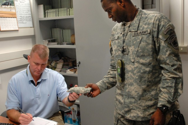 John Bratcher, personnel recovery specialist (left) issues a survival kit to Capt. Spenger Jeune of U.S. Army Africa G-6, Communications and Information directorate. USARAF  travelers are encouraged to visit the Personnel Recovery Directorate to take advanted of survival tools and training.