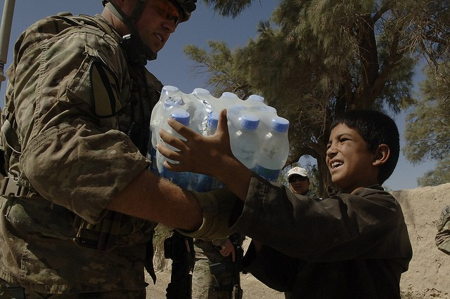 Sgt. Brian Ohler hands a case of water to a local boy while conducting a quality assurance check for a road project, members of Provincial Reconstruction Team Farah stopped to render assistance to the villagers whose building had caught fire.