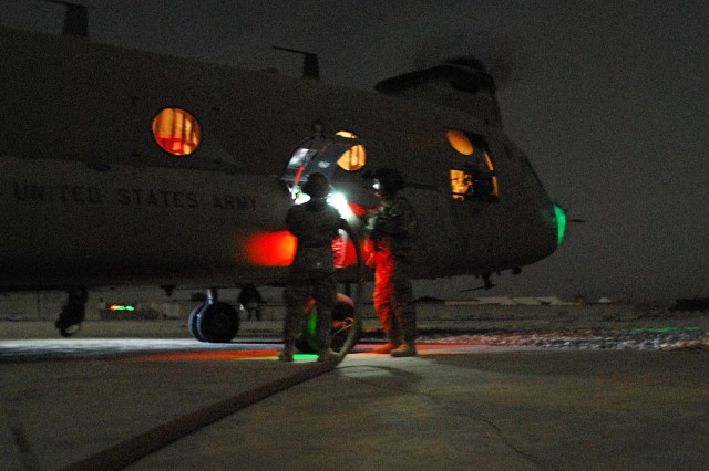 Soldiers refuel a CH-47F from Task Force Attack, 1st Air Cavalry Brigade, currently attached to 10th Combat Aviation Brigade, 10th Mountain Division, while waiting to pick up troopers they dropped off in eastern Afghanistan for night operations, July 17, 2011.
