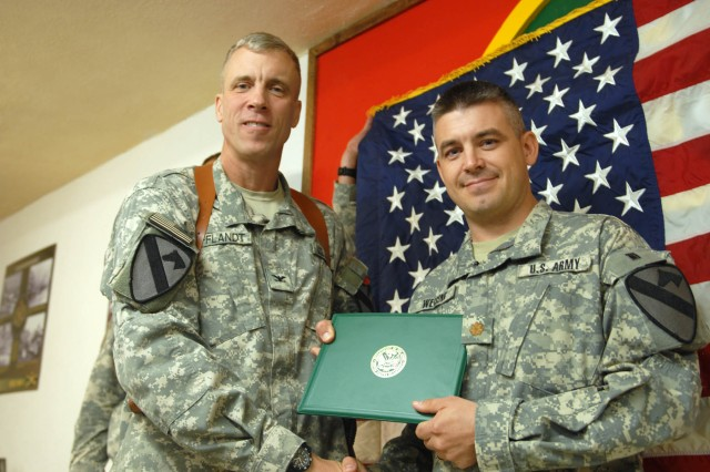 COS KALSU, Iraq -- Findlay, Ohio native, Maj. David Weising, the Chief of Operations for the 1st Advise and Assist Brigade, 1st Cavalry Division, receives his certificate of promotion from the Ironhorse commander, here, August 1.