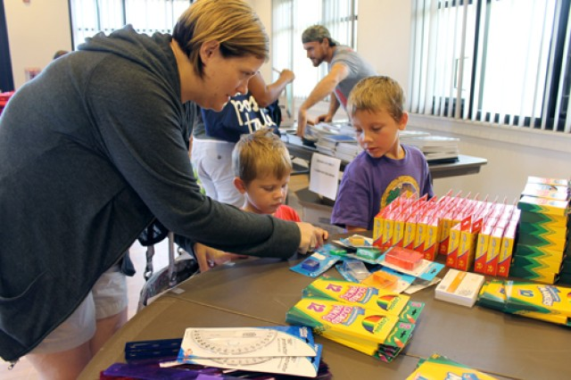 Army wife Erin McQuaig, of Schofield Barracks, helps her sons Connor (left) and Patrick McQuaig select school supplies at Operation Homefront's Back-to-School Brigade event at Schofield Barracks, July 29. The national nonprofit provided supplies to 200 military children on Oahu.