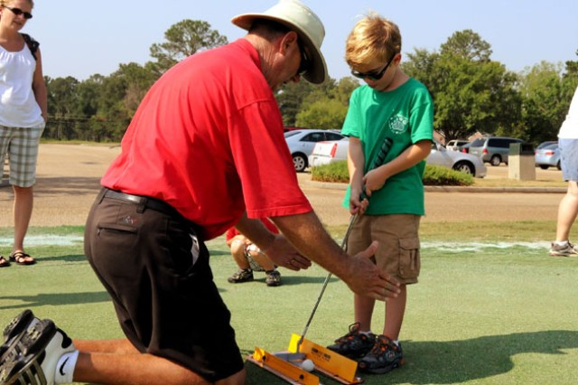 Ronnie Mobley, SWGC golf pro, works with Alerik Nedostup, 6, on the practice putting greens during the first EFMP golf clinic this summer.