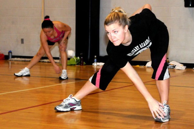 Courtney Vigil, military spouse, does crossover stretching during the 2011 Boot Camp session at Fortenberry-Colton Physical Fitness Facility at Fort Rucker, Ala., this year.
