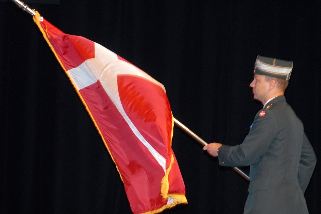 Danish Maj. Kenneth Algreen Starskov enters the stage with his country's flag for the international flag ceremony Aug. 8 at the Lewis and Clark Center, Fort Leavenworth, Kan.