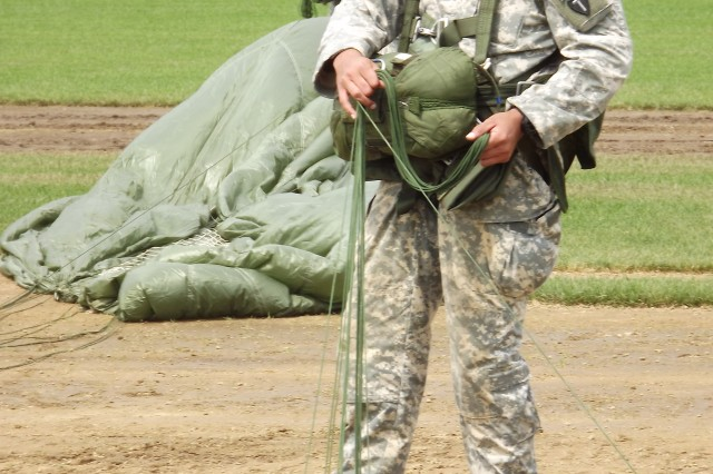 1st Lt. John Sutter from Bravo Company 143rd Infantry Regiment based in Bethel, Alaska packs up his parachute after his team landed on the drop zone in Kingston, Rhode Island for the 29th annual Leapfest on August 6, 2011.