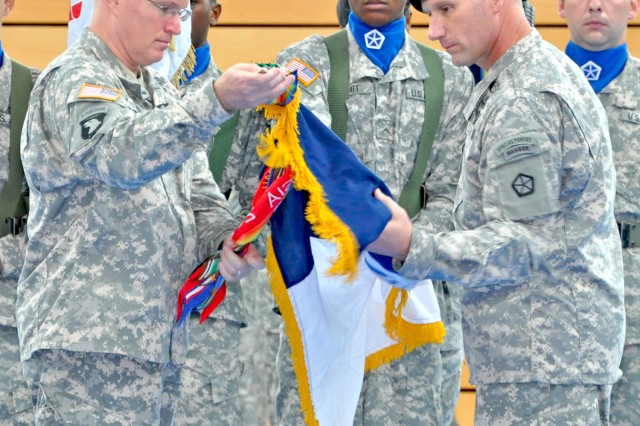 V Corps' Brig. Gen. Ricky D. Gibbs (left) and Command Sgt. Maj. William M. Johnson uncase the Corps' colors in a ceremony on Wiesbaden Army Airfield Aug. 12. The uncasing ceremony marked the official arrival of the unit, spearheading the transformation of U.S. Army Europe and follow-on of USAREUR Headquarters from Heidelberg to Wiesbaden next year.