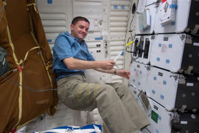 STS-135 mission specialist Rex Walheim performs temperature checks of the Space Tissue Loss Cell Culture Module in the middeck of Atlantis.
