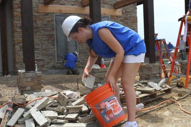 """Jennifer Wales, wife of a Fort Riley Soldier, gathers stone for the entryway of a house being built in Ottawa, Kan., for a Kansas National Guardsman who has PTSD. Around 400 volunteers in conjunction with """"Extreme Makeover: Home Edition"""" built the house in a week. The episode is scheduled to air in October."""
