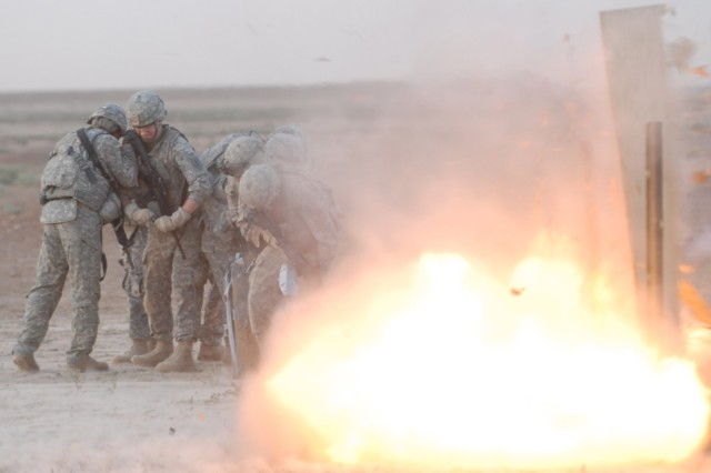 "CONTINGENCY OPERATING SITE WARRIOR, Iraq – Soldiers from 'Chaos' Company C, 1st Special Troops Battalion, 1st Advise and Assist Task Force, 1st Infantry Division, conduct room breaching drills by detonating C-4 plastic explosive to breach a locked door during Engineer Core Demolition Task Training at a demolitions range outside of Contingency Operating Site Warrior, Iraq, Aug. 11, 2011.  ""The range validates the training through live demolitions,"" said 1st Sgt. Harold Cole Jr., senior enlisted Soldier, Company C."