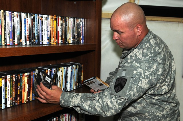 """CAMP ARIFJAN, Kuwait """" Staff Sgt. Shannon Biggs, 230th Sustainment Brigade, Tenn. Army National Guard, noncommissioned officer in charge of the campus and a Cornersville, Tenn. native., selects DVD's  to watch at the 230th Resiliency Campus here Aug. 16. Through establishments such as the 230th Resiliency Campus, Third Army is helping servicemembers, the strength of our nation, to sustain the fight and shape the future of the Middle East."""