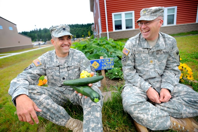 Lt. Col. Sean Kirschner, left, 23rd Chem. Bn. commander, and Maj. Scott Gould sit next to their battalion's garden Aug. 5.