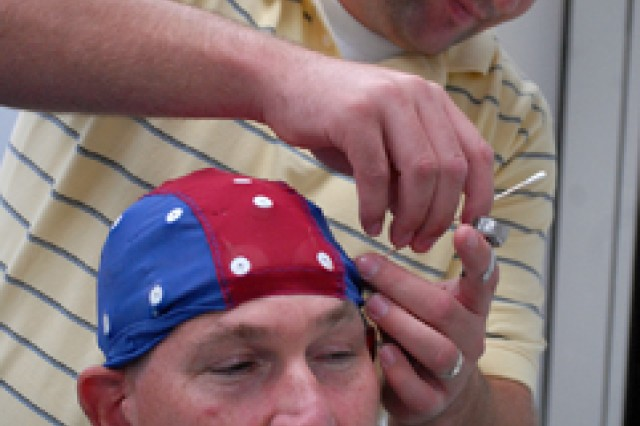 Travis Richardson, Arizona State University graduate and research associate with the Neuroscience of Leadership project, watches a connection monitor as he cleans the scalp of Chaplain (Maj.) David Schnarr, student in the 2011-02 Intermediate Level Education class, to ensure accuracy of an electroencephalogram cap Aug. 10, 2011, at Eisenhower Hall, Fort Leavenworth, Kan. Local leaders were sought to participate in the brain study, conducted by Arizona State University's W. P. Carey School of Business, sponsored by the Combined Arms Center's Center for the Army Profession and Ethic and Defense Advanced Research Projects Agency. The study seeks to identify trends among leaders through brain scans and supplementary information.