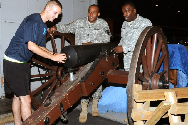 From left, Pvt. 2nd Class Steven Younker, Master Sgt. Caleb Green, and Sgt. 1st Class Frank Carroll check out one of the props for the 2011 Spirit of America show between rehearsals. Steven is playing a Union Soldier, Caleb is a vocalist and Frank is a drummer.