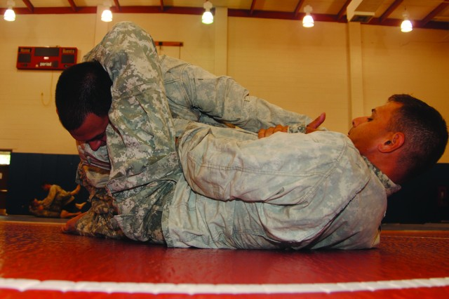Sgt. Oscar Morales (left), 258th Military Police Company, 519th Military Police Battalion, 1st Maneuver Enhancement Brigade, grapples with Spc. Alberto Quinones, also of the 258th, during combatives training Aug. 10 at Fort Polk's 1st MEB gym.